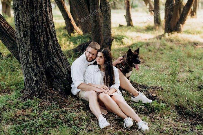 Amerikanischer Akita-Hund für einen Spaziergang mit einem Mann und einem Mädchen