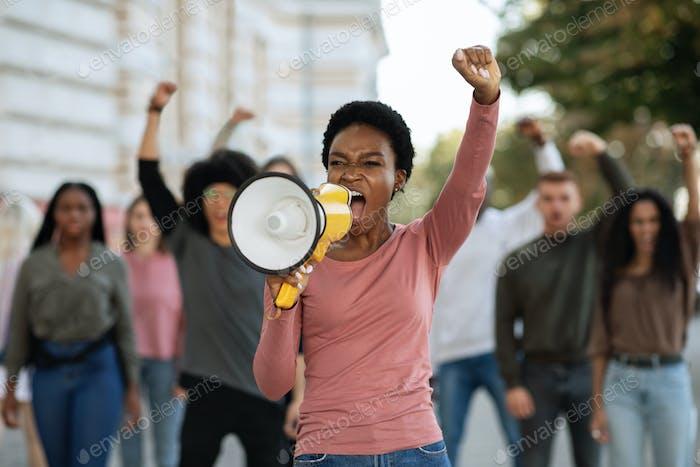 Schwarze Dame mit Megaphon führende Gruppe von Demonstranten