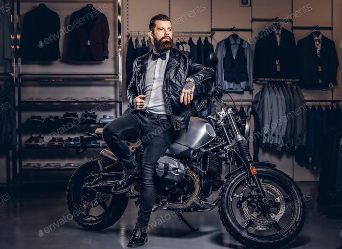 Жестокий мужчина, одетый в черную куртку, опираясь на ретро-спортивный мотоцикл в магазине мужской одежды.