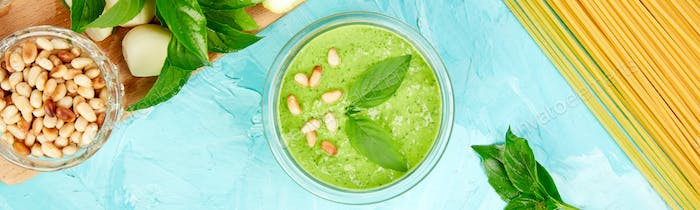Banner of Homemade pesto sauce in glass jar with ingredients.