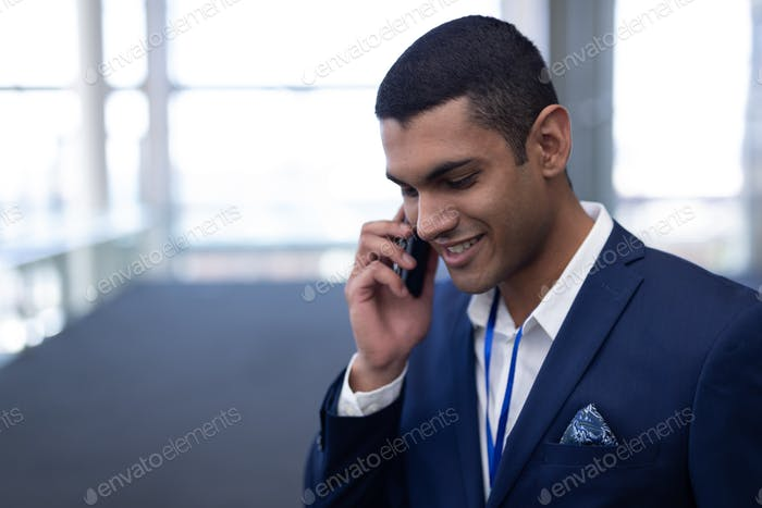 Businessman talking on mobile phone standing in modern office