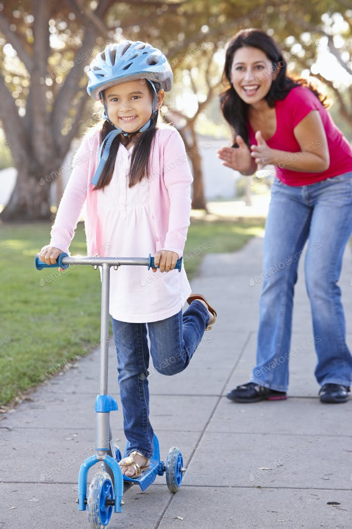 Mother Teaching Daughter To Ride Scooter