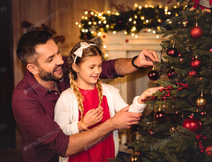 Smiling father and daughter decorating christmas tree