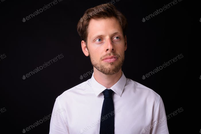 Face of handsome bearded businessman thinking and looking away