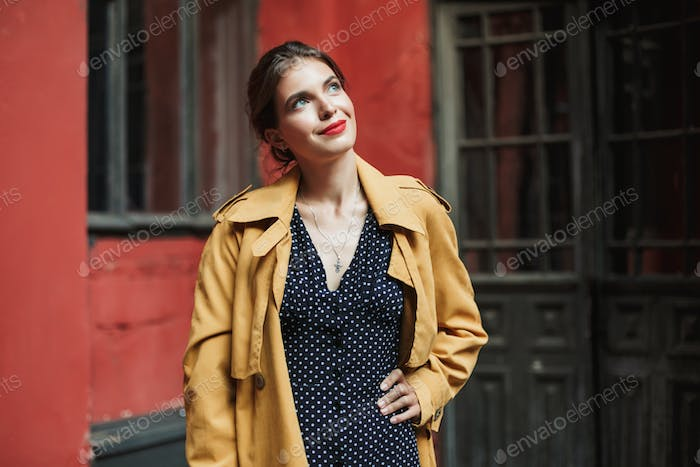 Young beautiful smiling woman in dress and trench coat dreamily