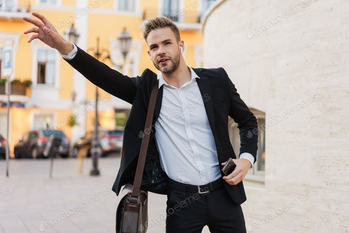 Handsome serious businessman using hitchhiking and holding mobile phone