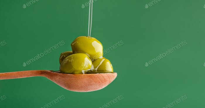 Green olives in spoon on green
