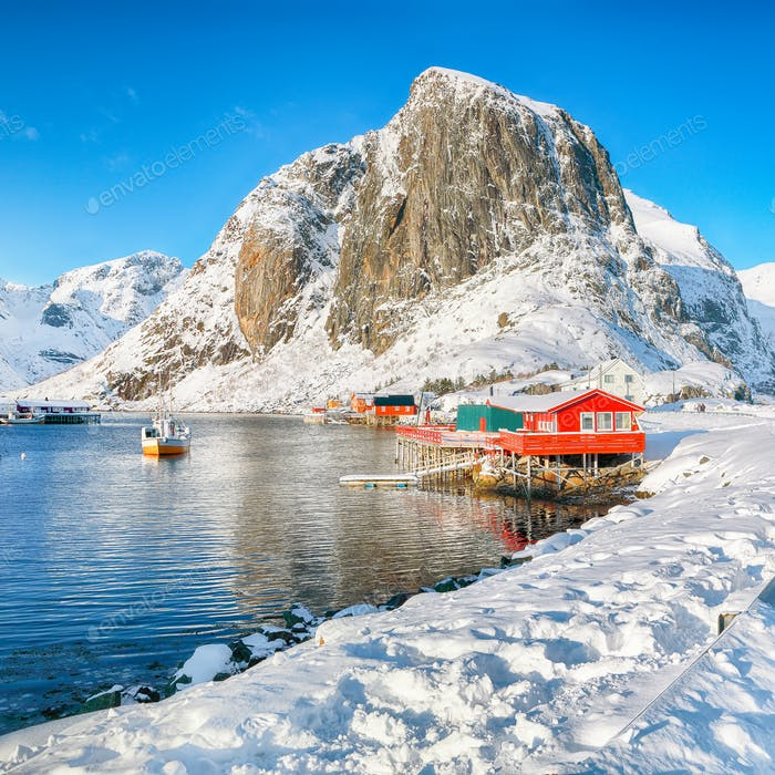 Winter view on Hamnoy village with port and Festhaeltinden mountain on background