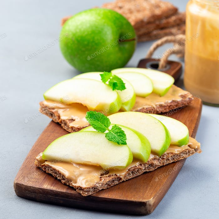 Sandwich with whole grain cracker, green apple slices and peanut butter, square
