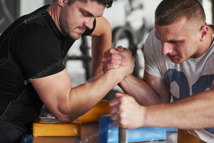 Fully concentrated on the game. Arm wrestling challenge between two men. Match on a special table