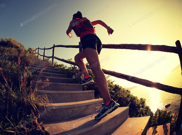 Woman runner trail running on seaside mountain stairs, training for cross country running.