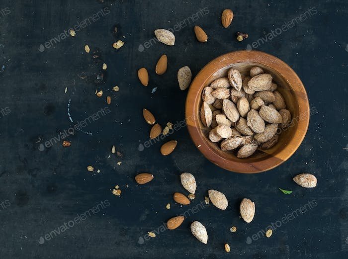 Wooden bowl of salty almond nuts in nutshell grunge dark backdrop, top view