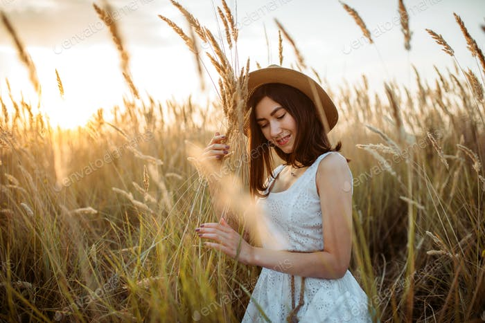 Woman in dress and straw hat holds wheat bouquet