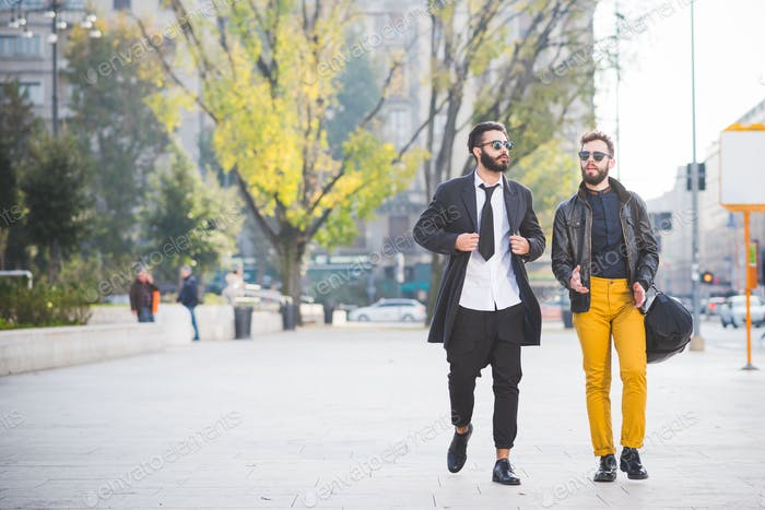 two young bearded blonde and black hair modern businessman, walk