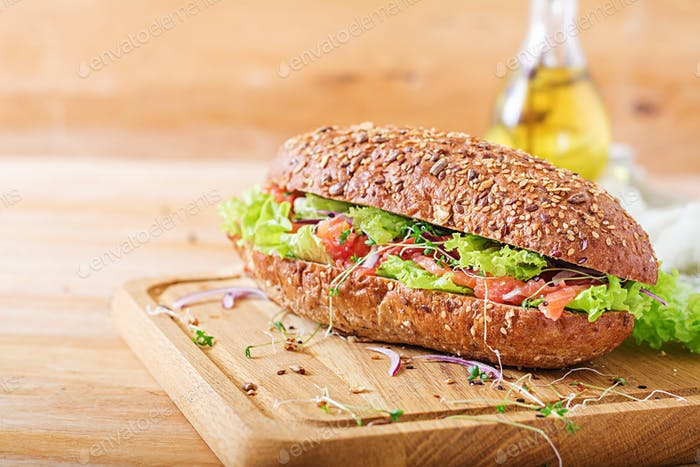 Salmon sandwich - smorrebrod with cheese cream and microgreen on wooden table.