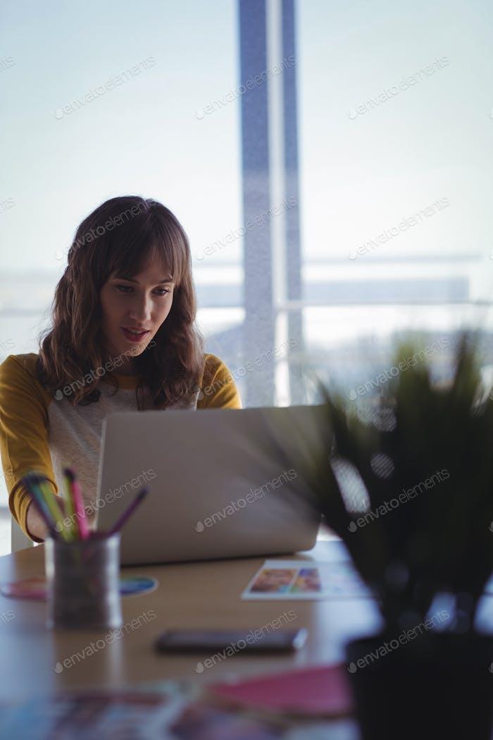 Entrepreneur working on laptop at office desk