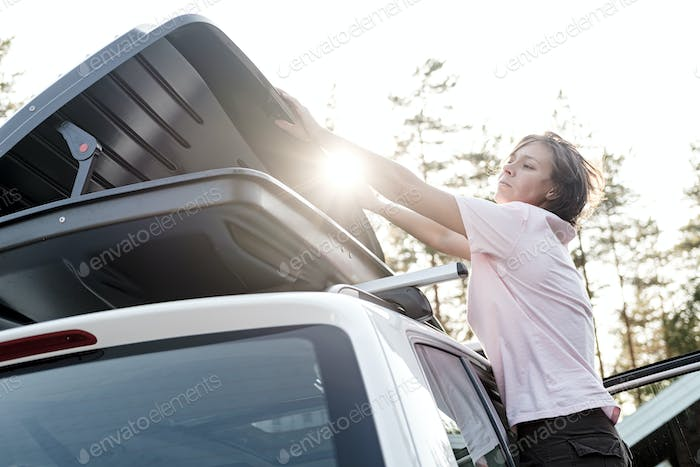 Woman closes a trunk loaded with things which is on the roof of a car