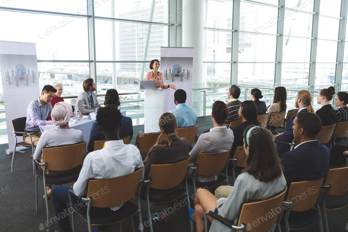 Businesswoman speaking in front of business people sitting at seminar in office building