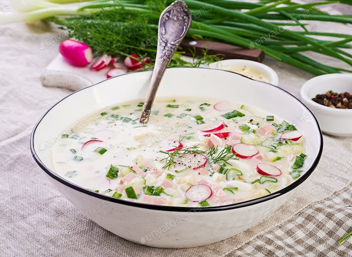Cold soup with fresh cucumbers, radishes, potato and sausage with yoghurt in bowl.