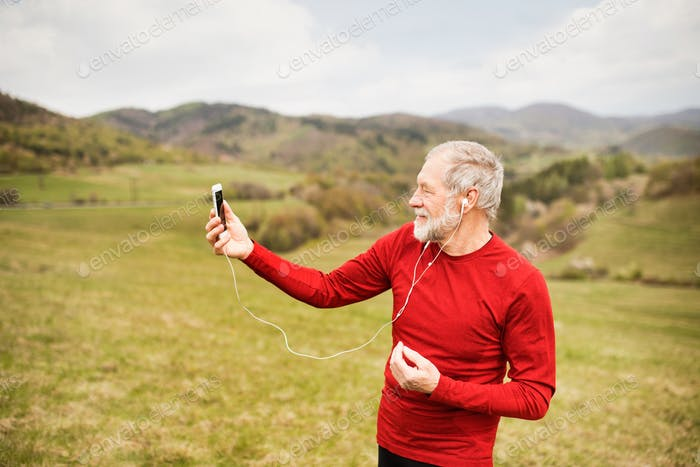 Active senior runner in nature taking selfie with smart phone.