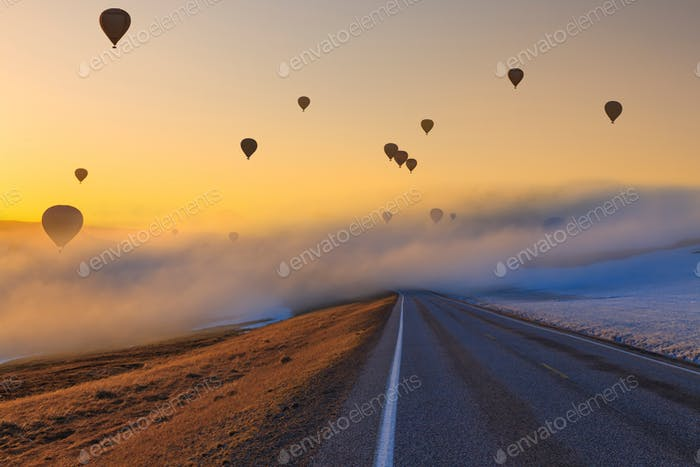 Hot air balloons over the road at sunset. Path and adventure concept