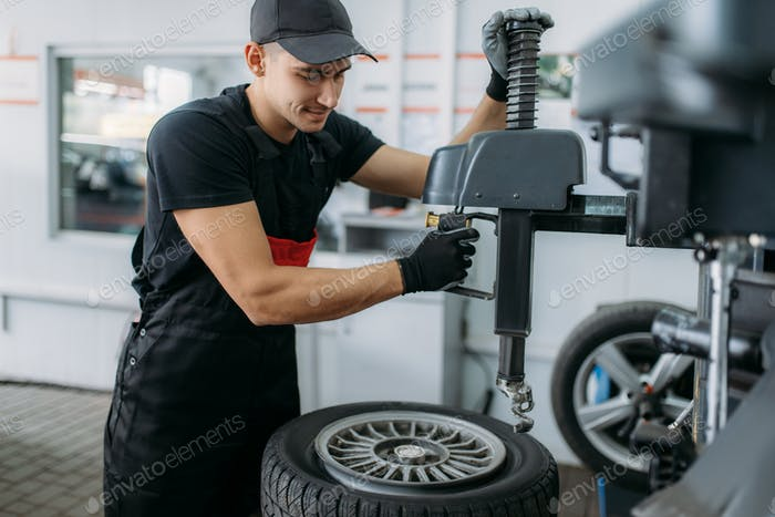 Mechanic fixing wheel on tire fitting machine