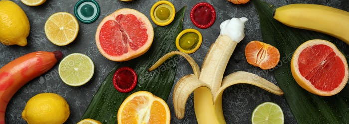 Sex concept with fruits and condoms on dark background