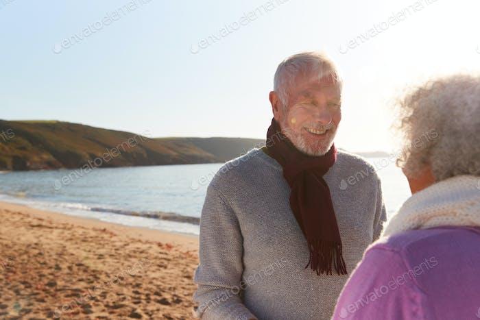 Liebevolle pensionierte Paar halten Hände stehend durch Ufer auf Winter Strand Urlaub gegen Abfackeln Sonne