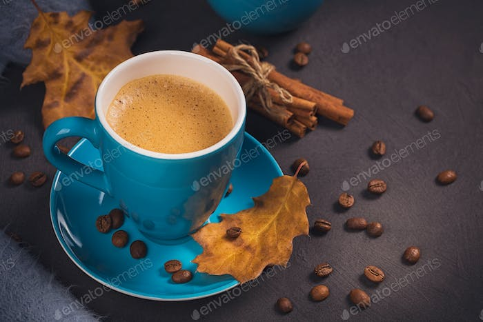 Blue cup of coffee with coffee beans and autumnal dry leaves