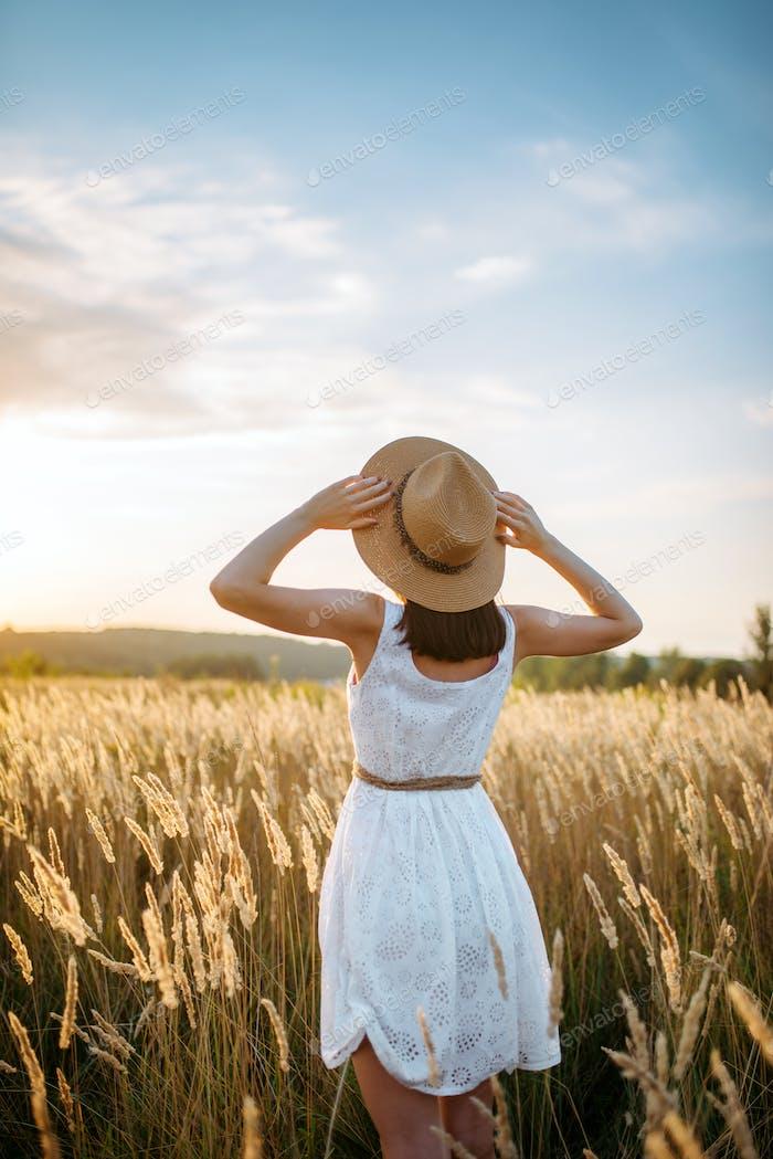 Frau im Kleid zu Fuß in Weizenfeld auf Sonnenuntergang