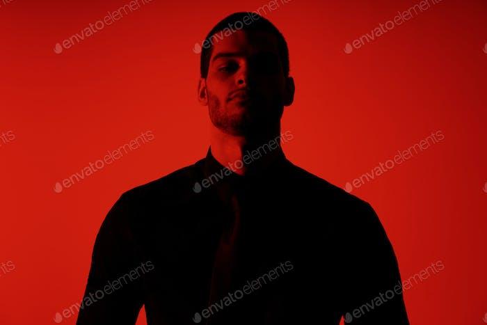 Silhouette eines jungen selbstbewussten gutaussehenden Geschäftsmann trägt schwarzes Hemd in rotem Licht