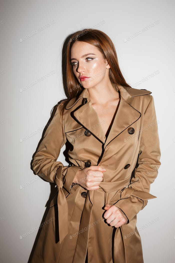 Young lady in trench coat standing and angrily looking aside