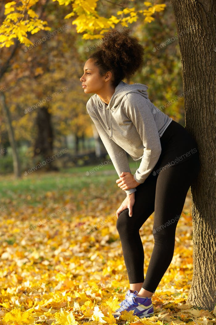 Schöne junge Frau stehend im Park nach dem Workout