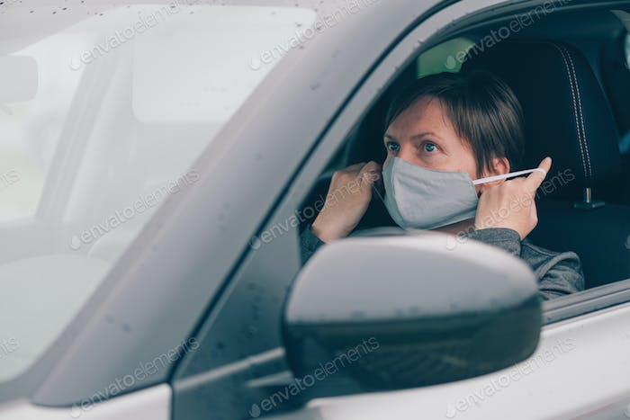 Woman wearing protective face mask in car during covid-19 pandemics