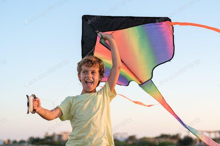 Happy boy having fun with kite