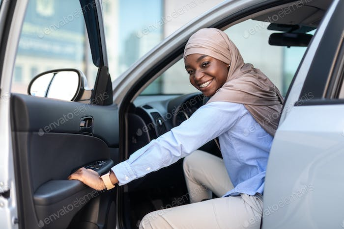 New Car. Happy black muslim businesswoman getting in luxury auto and smiling
