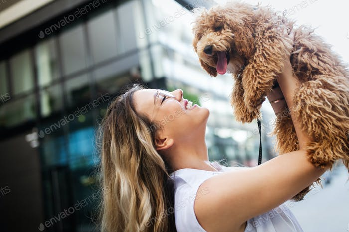 Happy woman with her dog smiling and palying outdoor