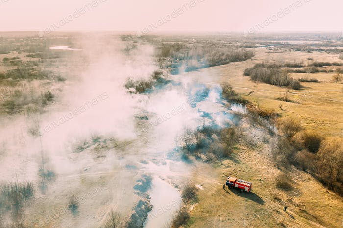 Aerial View. Spring Dry Grass Burns During Drought Hot Weather. Bush Fire And Smoke. Fire Engine