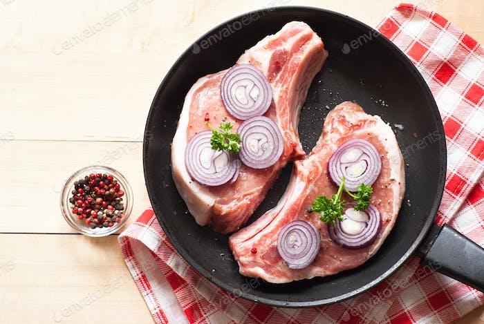 Rohes Schweinefleisch in einer Pfanne.