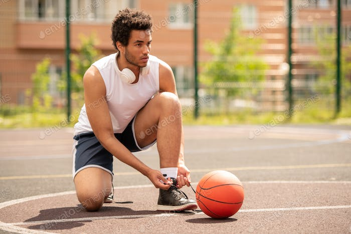 Young professional basketball player tying shoelace of sneaker