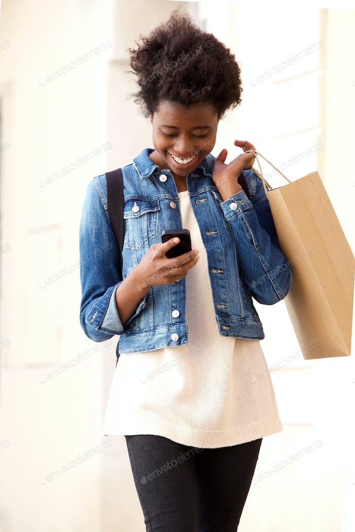 Happy Afro American Mädchen Blick auf Handy mit Einkaufstasche