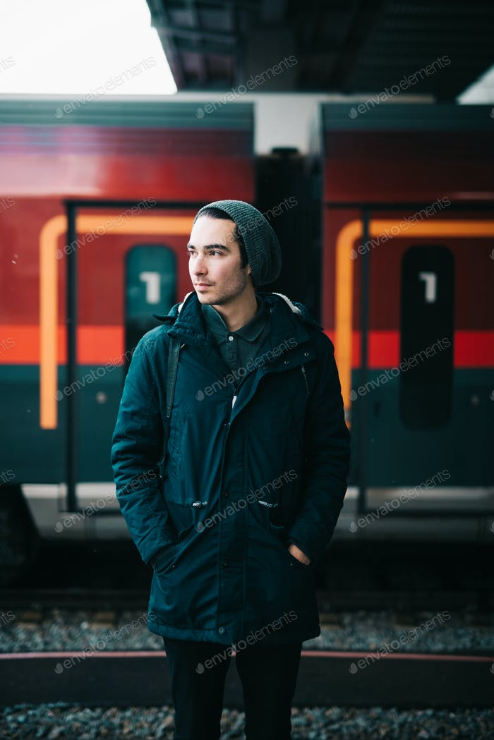 Young man standing in front of a train