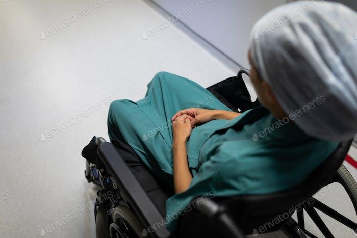 Hohe Ansicht einer kaukasischen Patientin sitzt auf einem Rollstuhl auf dem Krankenhauskorridor