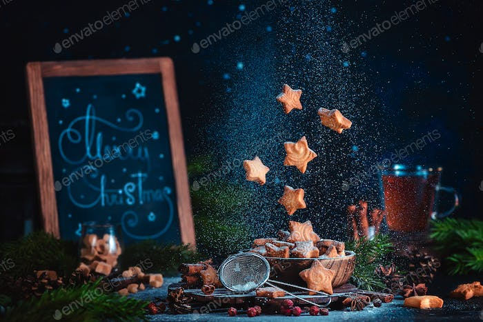 Flying star-shaped cookies with sugar powder and Merry Christmas lettering. Traditional baking