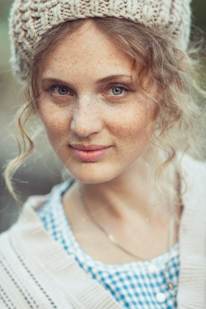 Funny attractive girl with freckles and curly hair