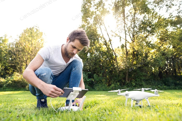 Young hipster man with drone. Sunny green nature.