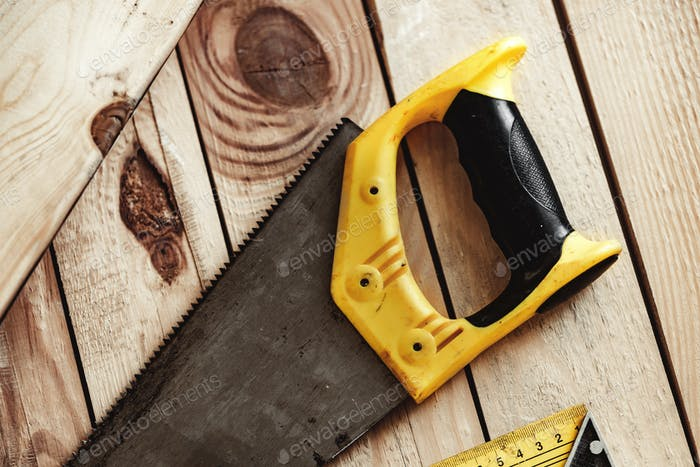 Hand saw on a wooden table in carpentry workshop
