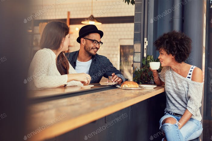 Happy young people sitting in a cafe