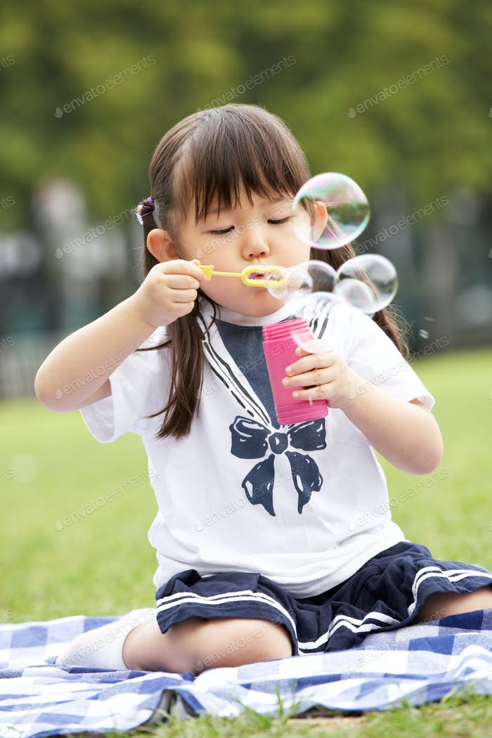 Young Chinese Girl In Park Blowing Bubbles