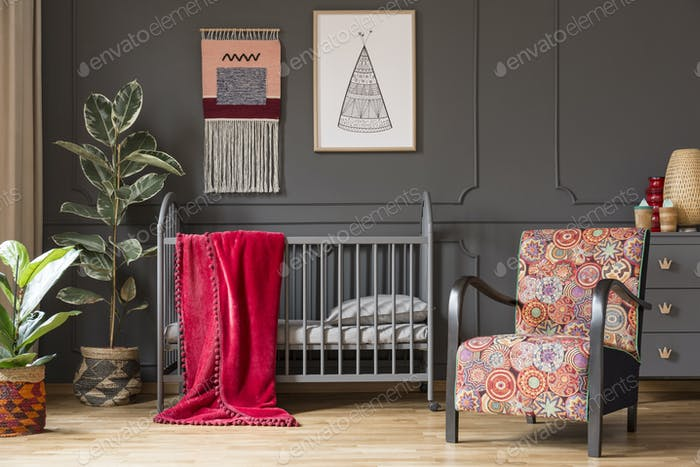 Patterned armchair next to baby's bed with red blanket in grey b